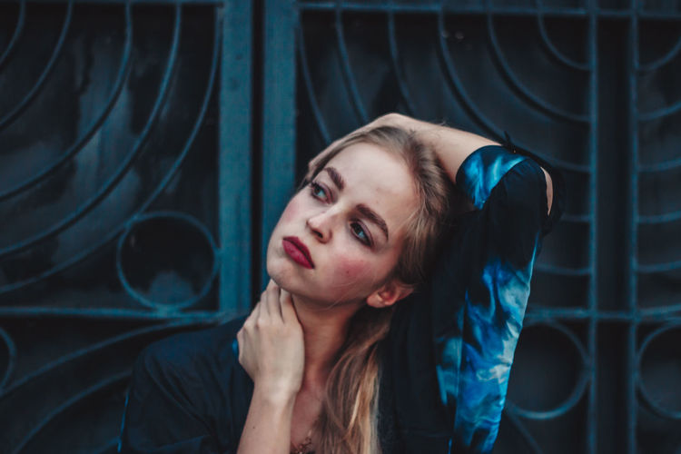 Beautiful woman looking away while standing against metal gate