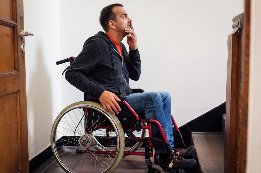Accessibility Adult Casual Clothing Concept Conceptual Differing Abilities Indoors  Looking One Man Only One Person People Physical Impairment Real People Sitting Stairs Steps Technology Wheelchair Wheelchair Access