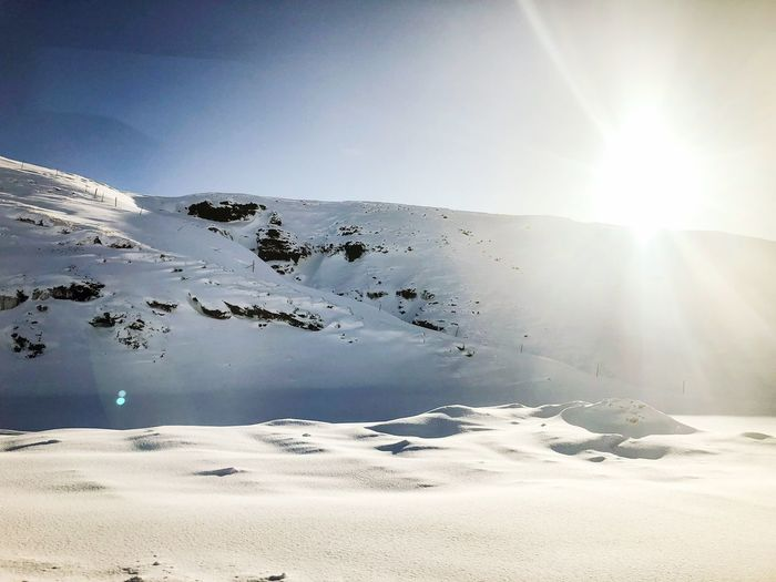 A view from the 🚌 bus Covered In White Covered In Snow Snowymountains Sunlight Cold Temperature Sun Lens Flare Day Outdoors No People Winter Sky Clear Sky Water Landscape