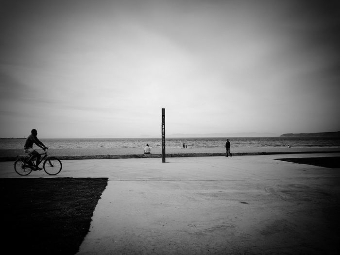 Man riding bicycle on beach against sky