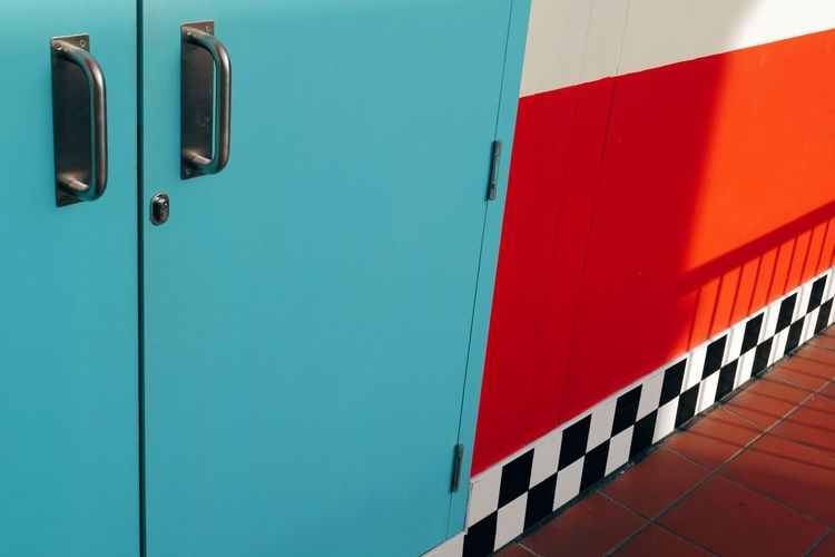Close-up of red door and blue wall