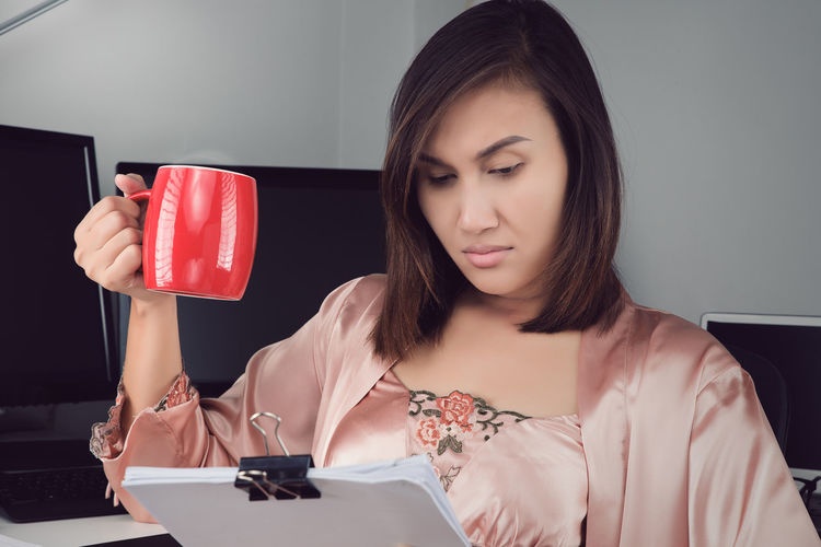 Asian woman in satin nightgown drinking coffee to get some energy for working overtime at home Backlog Businesswoman Check Coffee - Drink Coffee Cup Deadline Diligent Examine Exhausted Home Office Insomnia Investigate Job Night Nightwear Operate Overtime Sleepless URGENT Woman Work Working