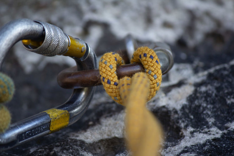 High angle view of rope tied over harness on rock