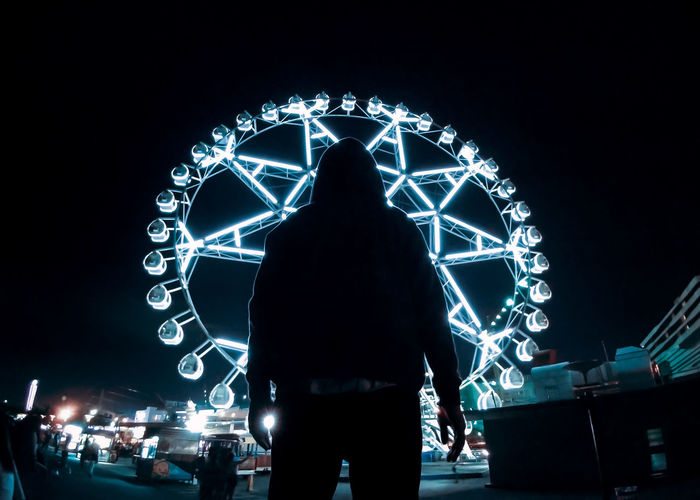 Rear view of silhouette man standing against illuminated lights at night