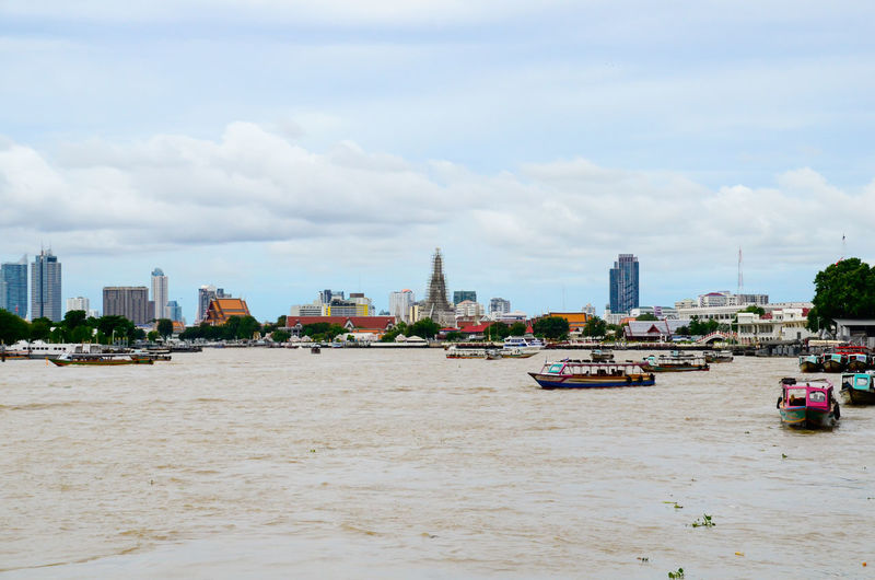 Boats on chao phraya river against cloudy sky