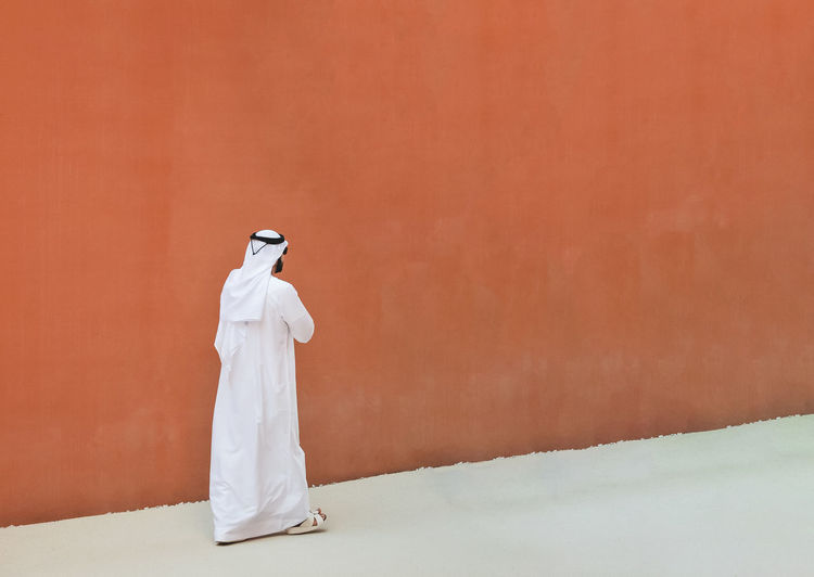 Rear view of woman standing against white wall