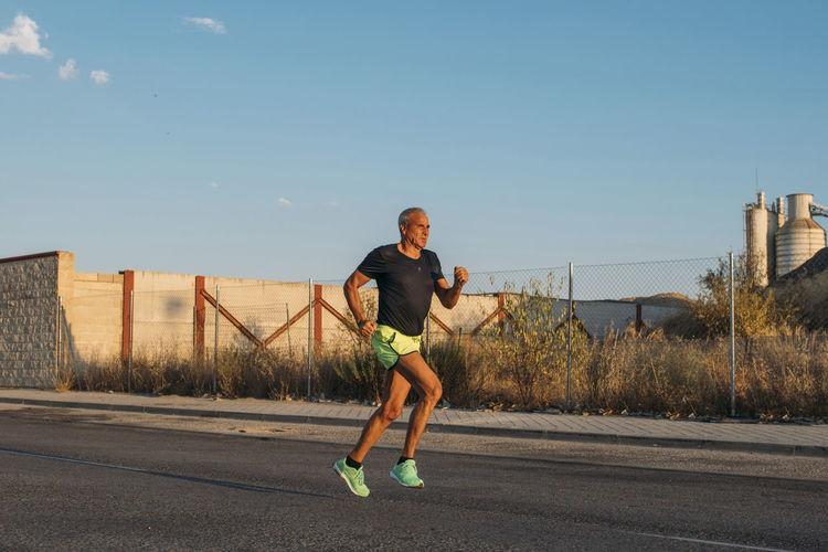 Full length portrait of man running on road against sky