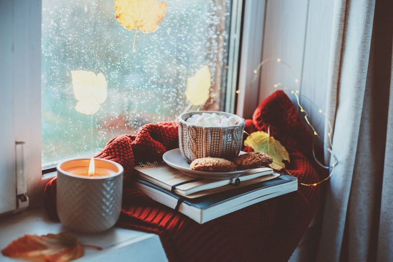 cozy autumn morning at home. Hot cocoa with marshmallows and candle on window in rainy cold day. Spending holidays at home. Window Indoors  Food And Drink Home Interior No People Cup Still Life Breakfast Autumn Season  Fall Cold Days Cozy Hygge Cocoa Marshmallows Candle Candlelight Sweater Relaxing
