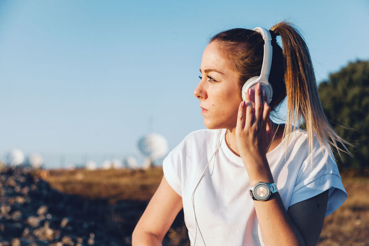 Young woman listening over headphones while sitting on land against sky