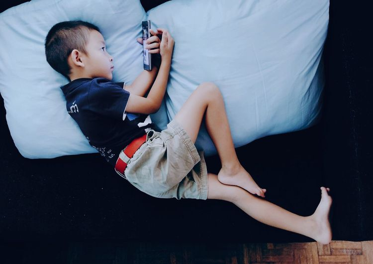 High angle view of boy using smart phone on sofa at home
