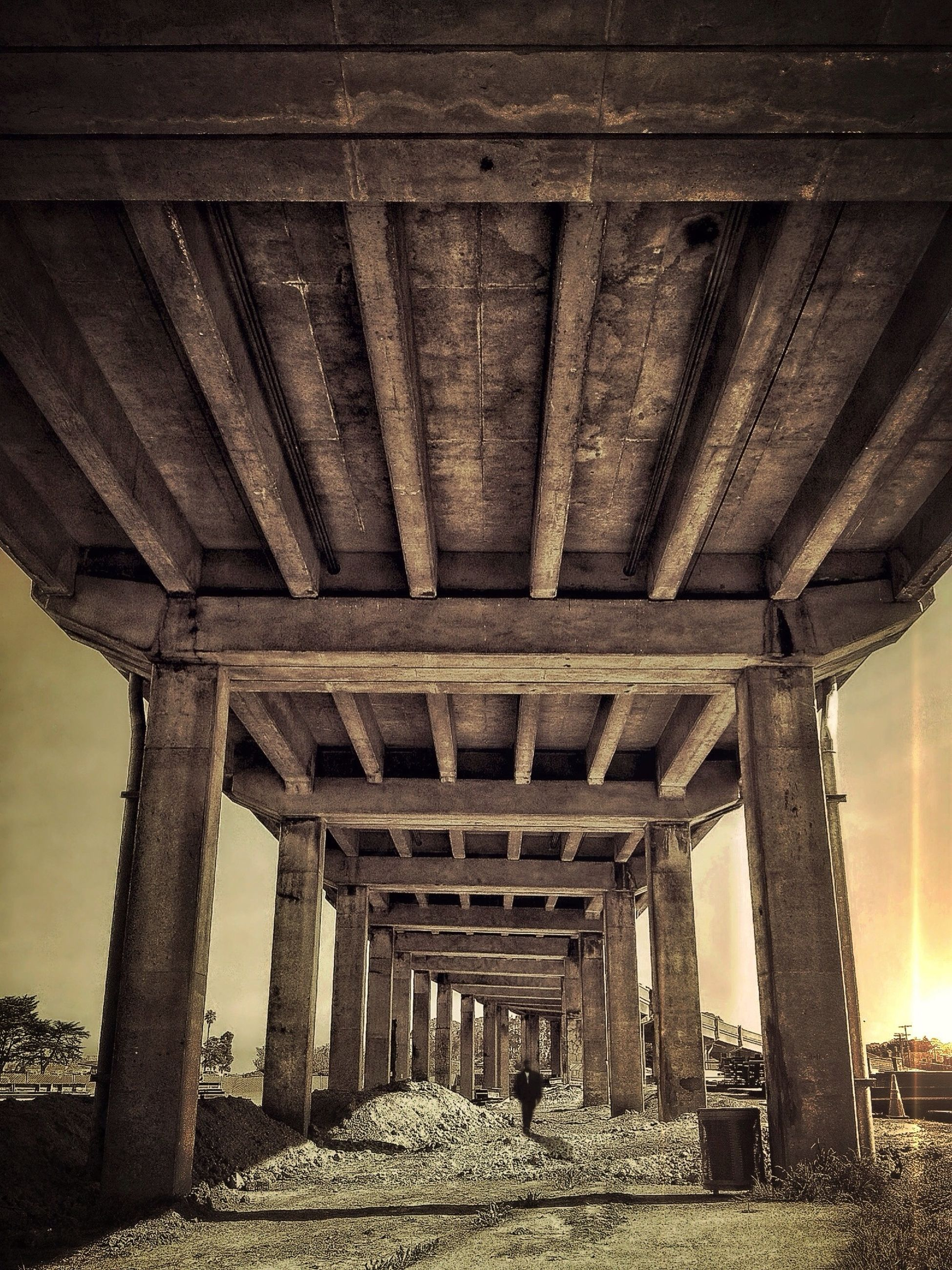 built structure, architecture, architectural column, the way forward, ceiling, column, indoors, sky, connection, diminishing perspective, bridge - man made structure, support, in a row, low angle view, sunlight, vanishing point, below, arch, day, bridge