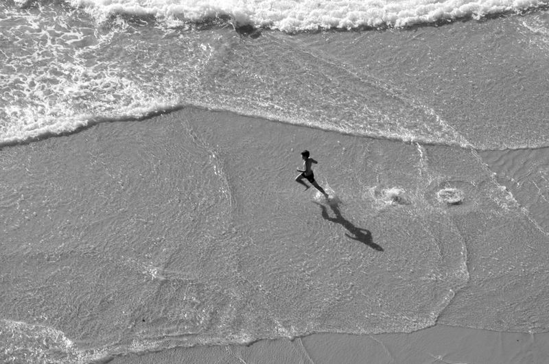 High Angle View Of Boy Running On Wet Shore