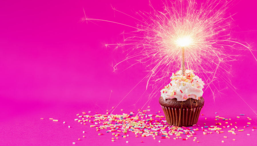 Birthday Cupcake with a sparkler at pink background Cake Cupcake Food Sweet Food Sweet Indulgence Food And Drink Pink Color Celebration Dessert Freshness Baked Temptation Studio Shot Sprinkles Event Unhealthy Eating No People Close-up Ready-to-eat Icing Sparkler Cupcake Holder Sparks Birthday Candles