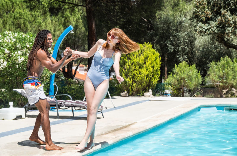 Friends enjoying by swimming pool during summer