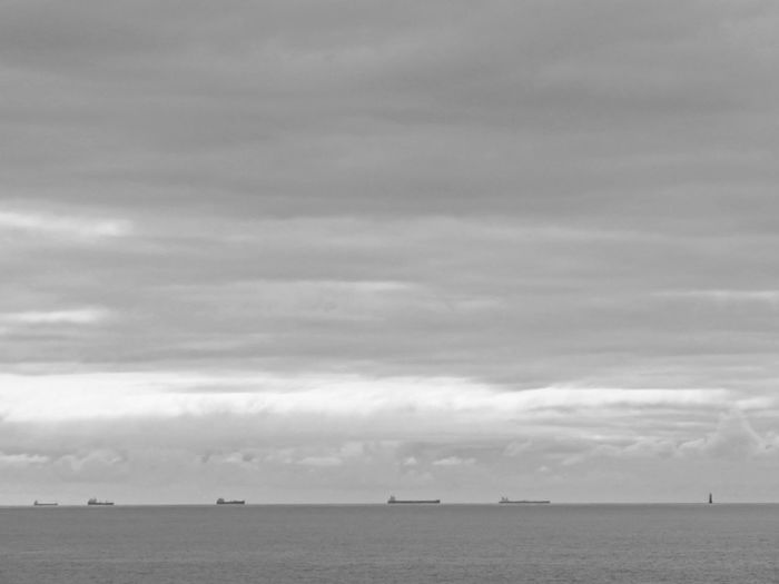 Five large boats aligned with an OCEAN lighthouse Boats Large Ocean Boats Large Boats Alignment Five Boats Out At Sea Horizon Over Water Horizon Lighthouse In Ocean Water Bnw Black And White Sea Photography