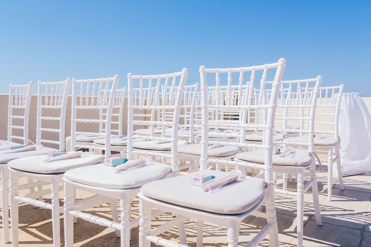 Empty chairs and tables at beach against clear blue sky