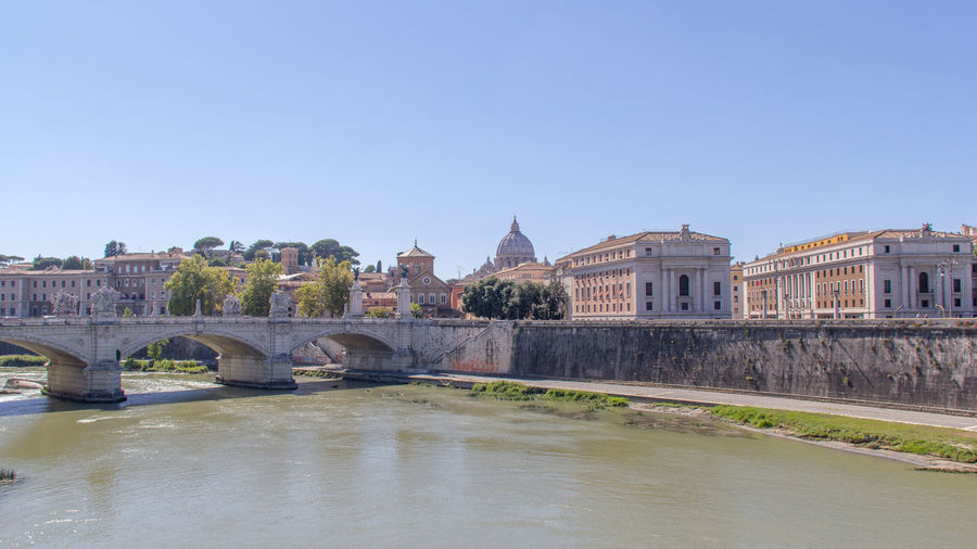 Arch Bridge Over River With St Peter Basilica In Background Against Clear Sky
