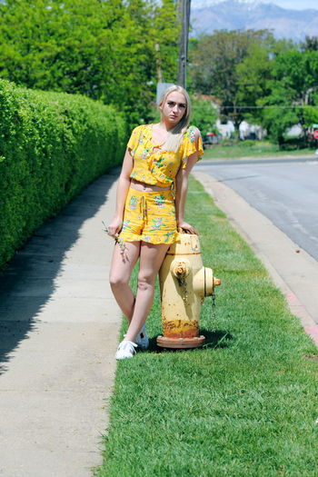 Green Sidewalk Summertime Adult Casual Clothing Day Emotion Fire Hydrant Front View Full Length Girls Grass Leisure Activity Looking At Camera Nature Neighborhood One Person Outdoors Plant Portrait Real People Teen Tree Women Yellow Color