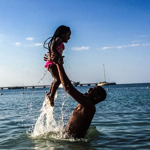 Side View Of Smiling Father Lifting Daughter While Standing In Sea Against Sky
