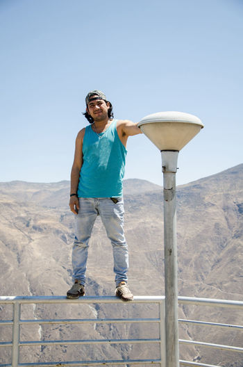 Full length of man standing on railing against mountains and clear sky