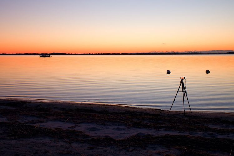 Silhouette of tall nature photographer at tripod taking picture on the beach at sunset time