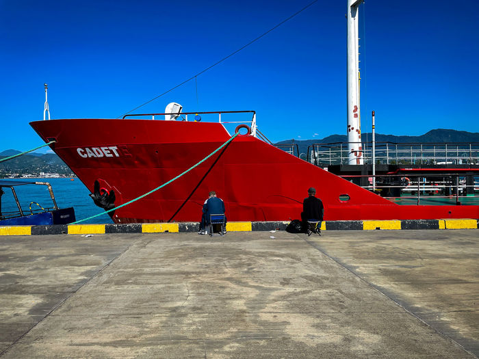 Red ship in sea against clear blue sky