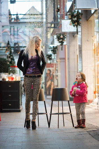 Full length of woman with daughter in shopping mall