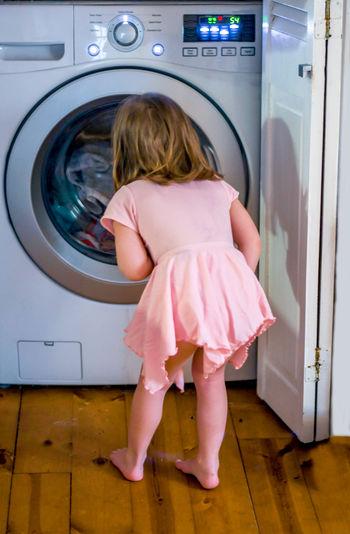 Rear view of girl looking at washing machine