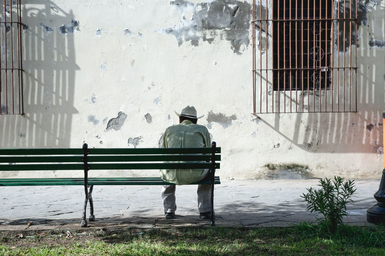 Rear view of man sitting on bench against building