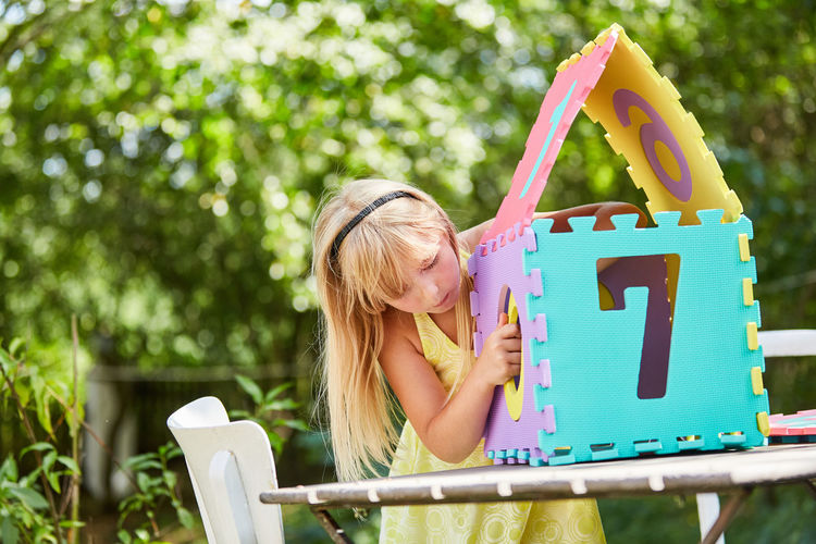 Girl making model home with puzzle at table in park