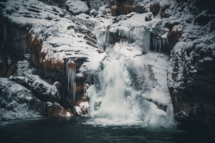 Scenic view of frozen waterfall by lake