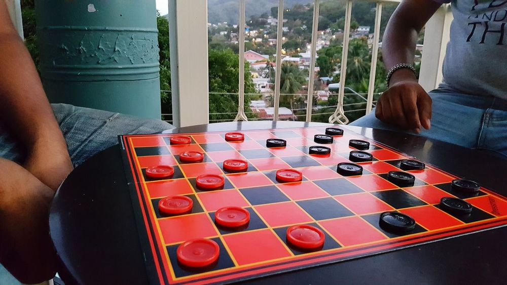 Human Hand Checkers Outdoors Board Game People Houses In Background Red And Black Colour Game On Intense