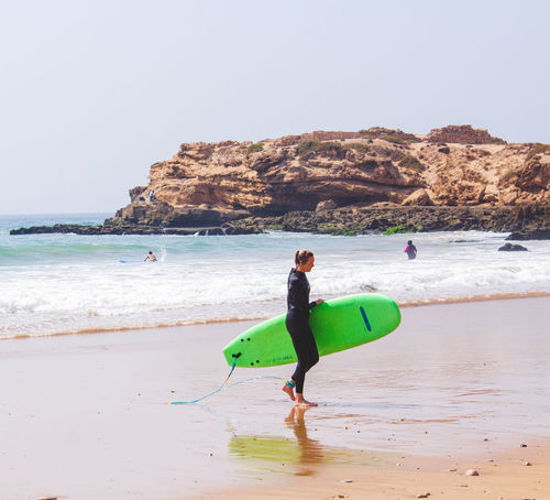 Surfer Coming Back from a Surf Session Surf Surfer Aquatic Sport Beach Beauty In Nature Day Full Length Horizon Over Water Incidental People Land Leisure Activity Lifestyles Nature People Real People Sand Sea Sky Sport Surface Surfing Surfing Competition Taghazout Bay Taghazout Surfing Water