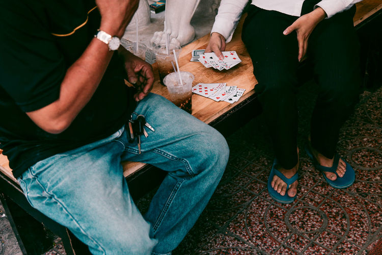 Low Section Of People Playing Cards