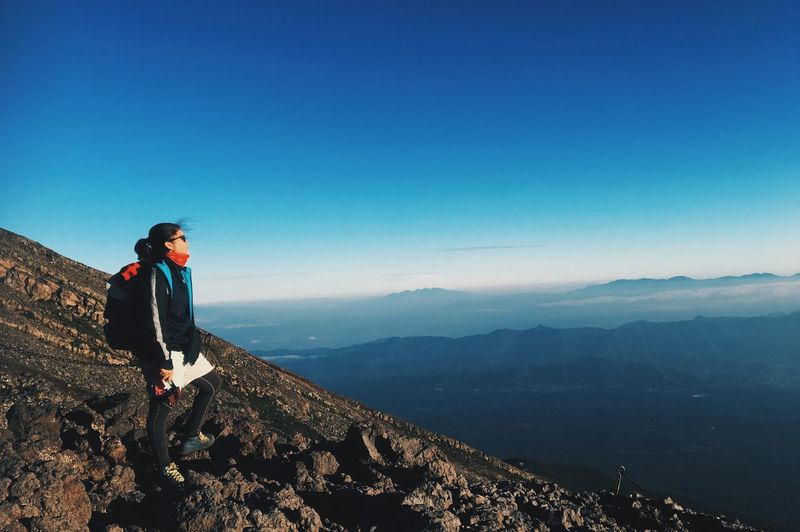 Woman standing on mountain against clear blue sky