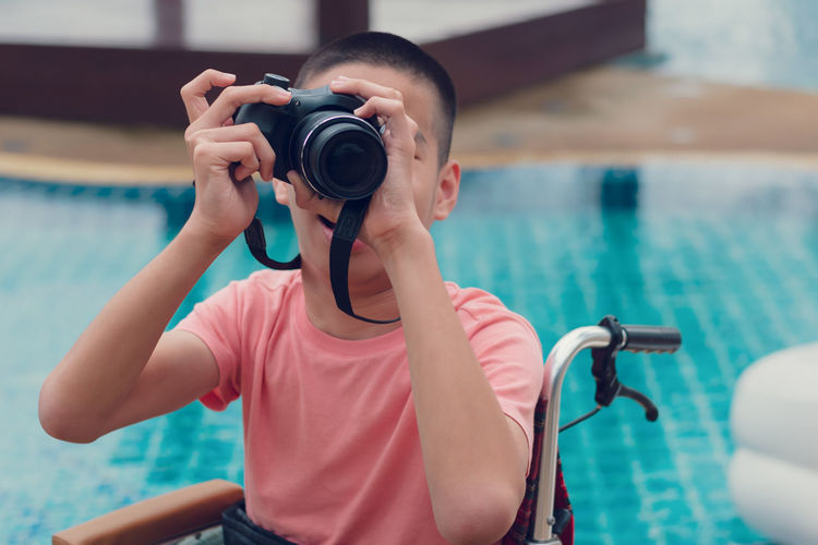 Cheerful boy photographing through camera by swimming pool