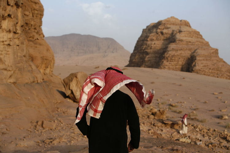 Rear view of man wearing traditional clothing in desert