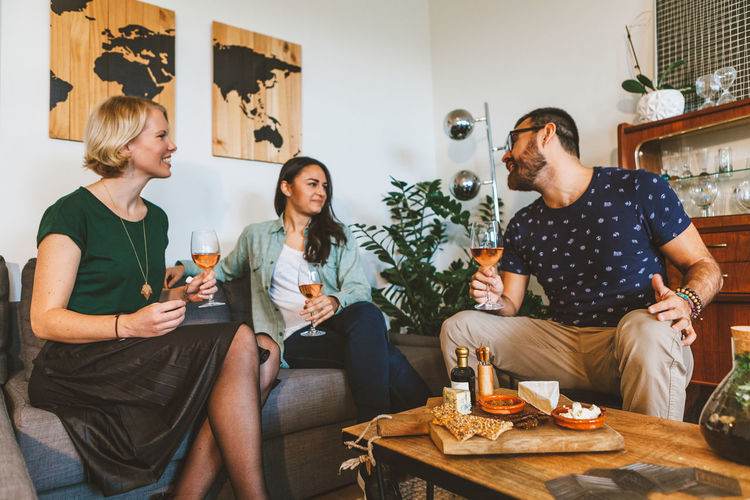 Friends Relaxing Young Alcohol Appetizer Casual Clothing Chatting Cosy Living Day Drink Food Food And Drink Friendship Indoors  Leisure Activity Party Real People Sitting Sofa Three Quarter Length Togethernes Togetherness Wine Young Adult Young Women