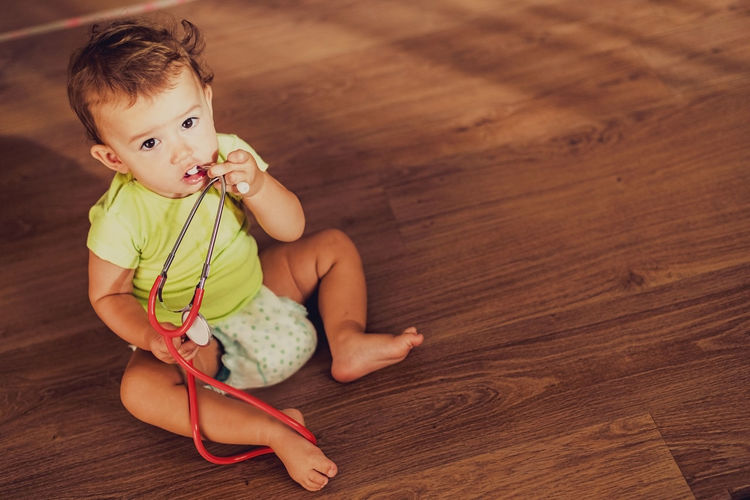 High angle view of baby girl sitting on floor at home