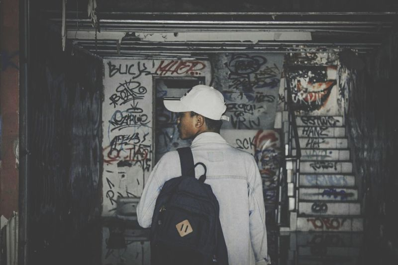 Rear view of man standing by graffiti on wall