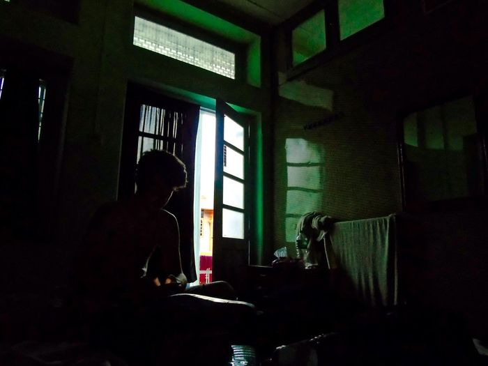 Hiding in a dark room from the hot midday sun in Moulmein, Burma. After we crossed the friendship bridge between Thailand and Myanmar, we embarked on a two day long journey from the border to Dawei. We stopped in Moulmein to stay overnight and visited Myanmar's biggest island. Dark Travel Burma Day Home Interior Indoors  Inside A Room Myanmar Myanmarphotos One Person People Photography Real People Single Light Source Sitting Window