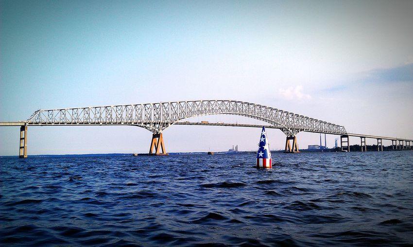 American flag on distance marker in sea against francis scott key bridge