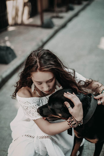 Young hippie woman in white boho blouse and skirt hugging black dog in the street in summertime