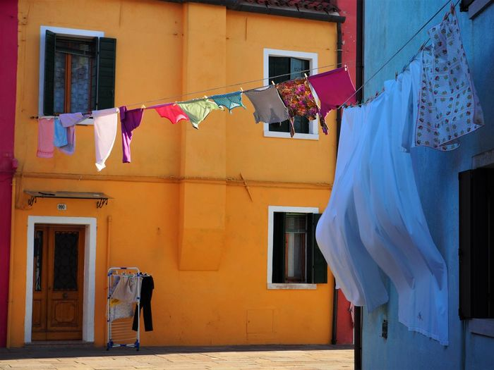 Low angle view of clotheslines by buildings