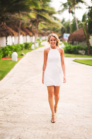 Dress Beautiful Woman Beautiful Women Day Full Length Happiness Leisure Activity Lifestyles Looking At Camera Nature One Person Outdoors Portrait Real People Smiling Standing Tree Vacations Walking Women Young Adult Young Women