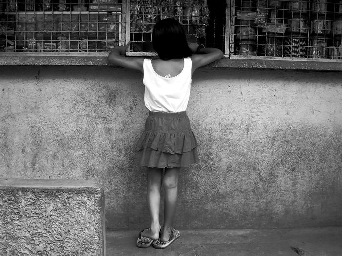 Rear View Of Girl Standing Next To Shop Window