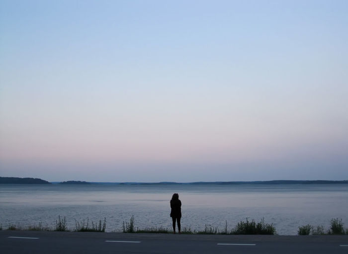 Silhouette Of Woman Standing At Water's Edge