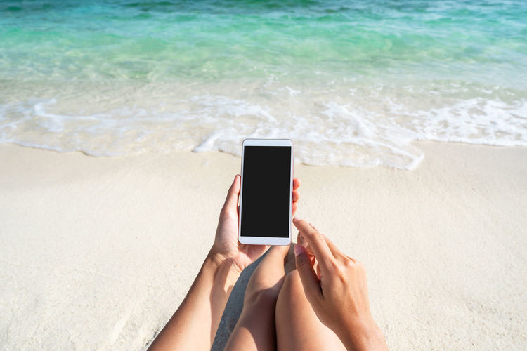 Midsection of man using mobile phone at beach