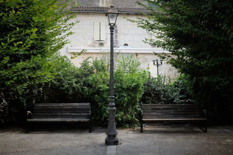Gas light amidst empty benches against building
