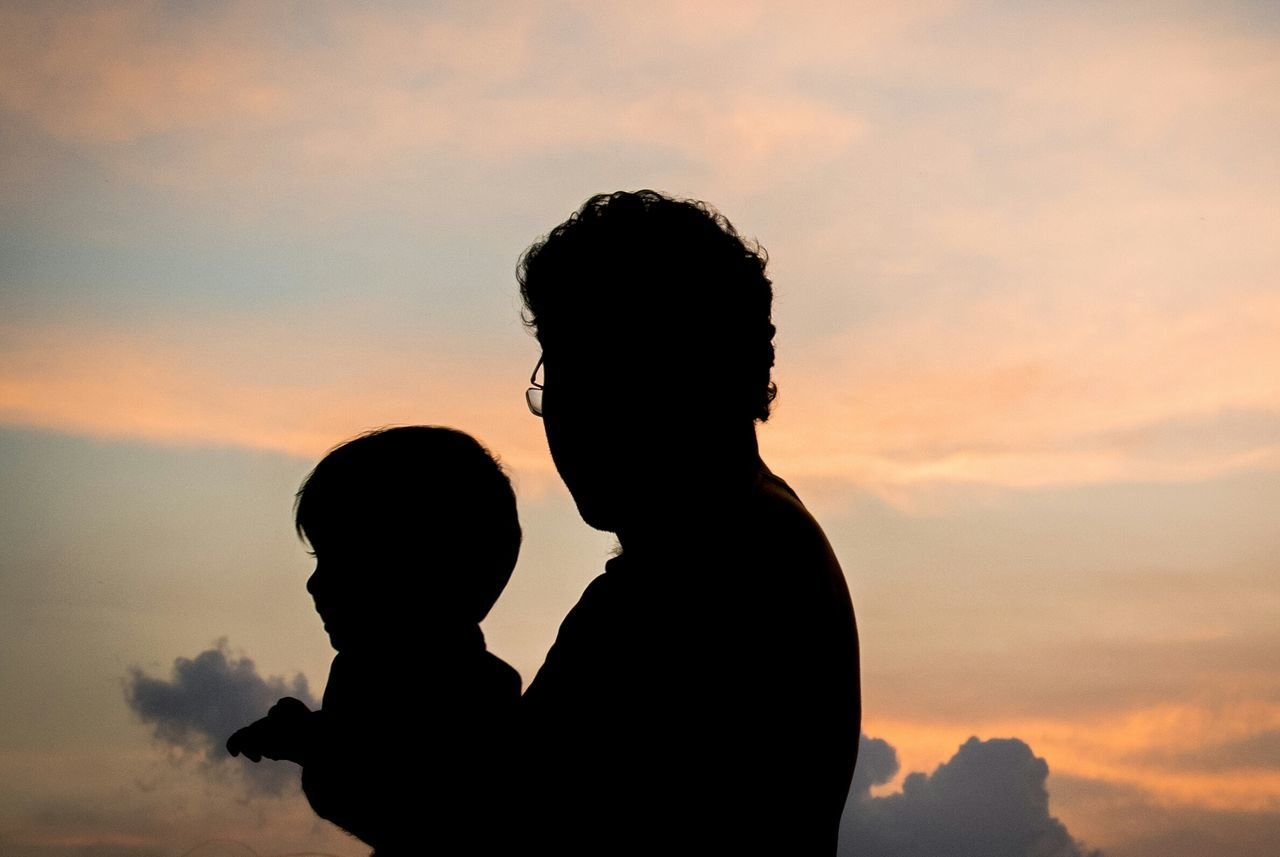 Silhouette father and son against sky during sunset